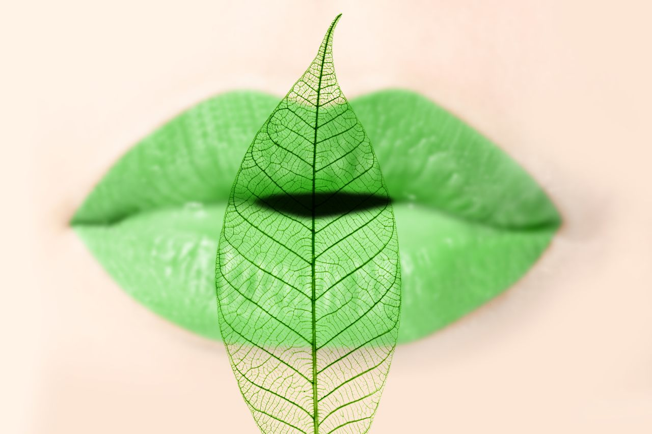 light green leave in front of a female mouth with green lips