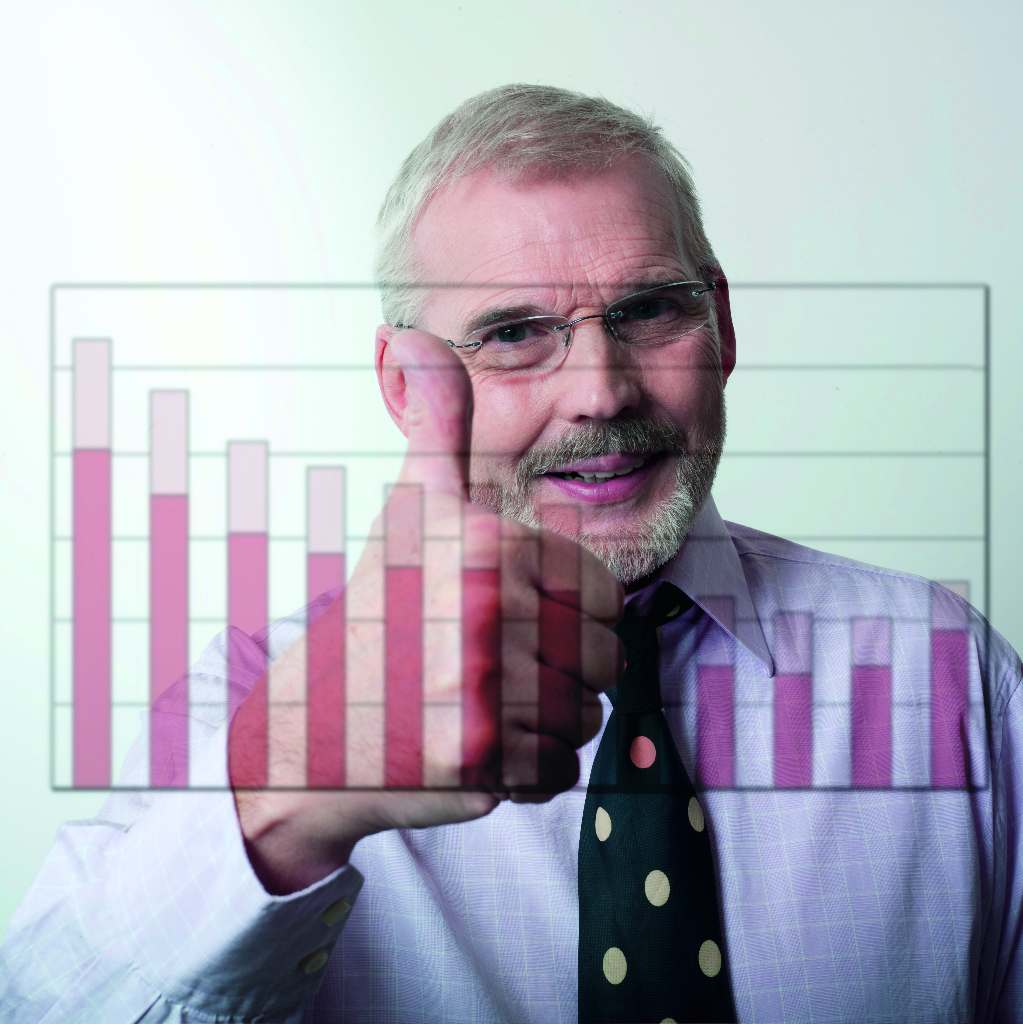 a man behind a graph will column holding a thumb up