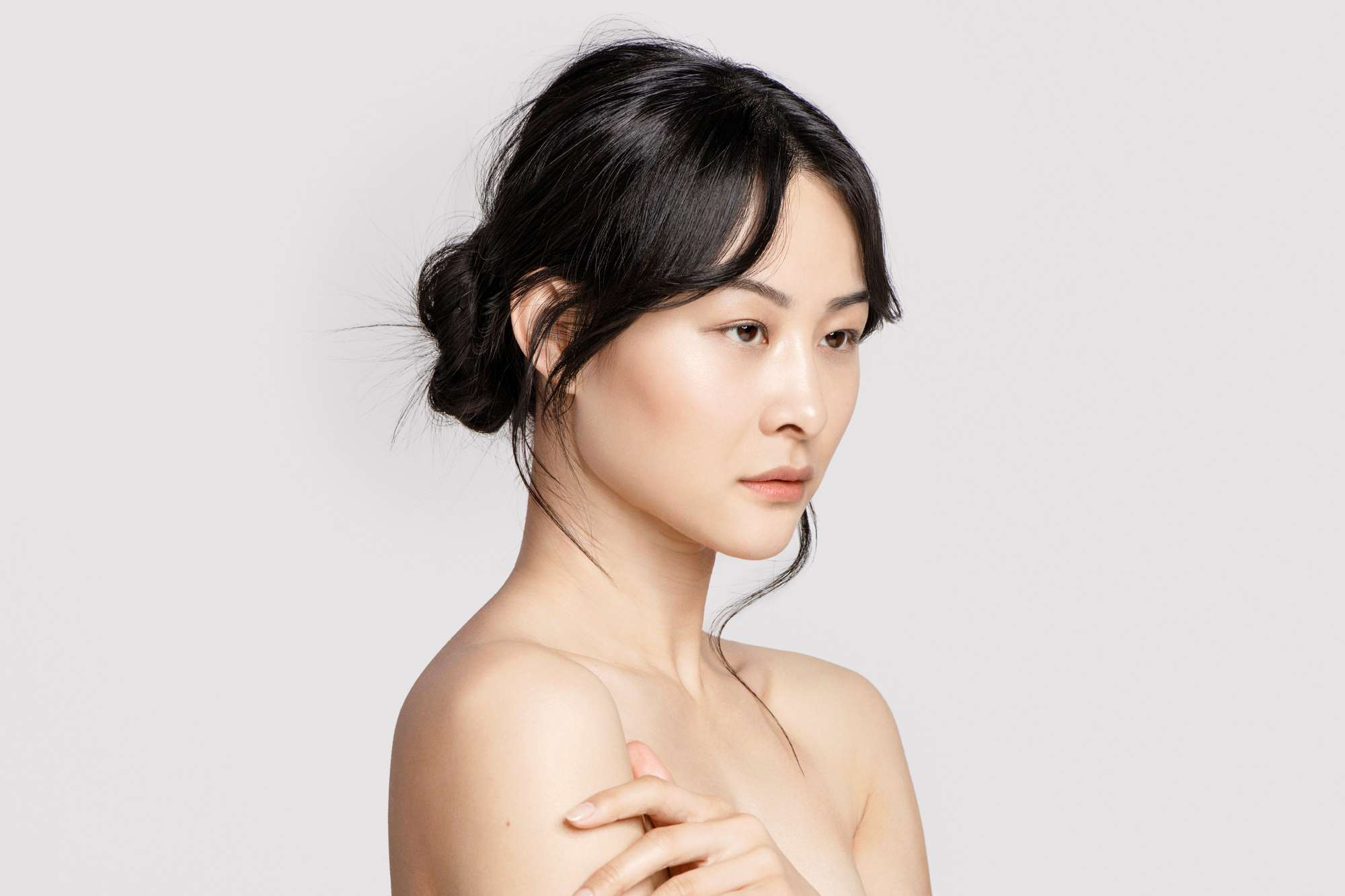 Asian female with naked shoulders in front of a white background