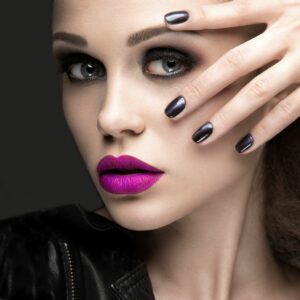 Women with pink lipstick holding her hand from the left side over her chest. Nails are black-coloured