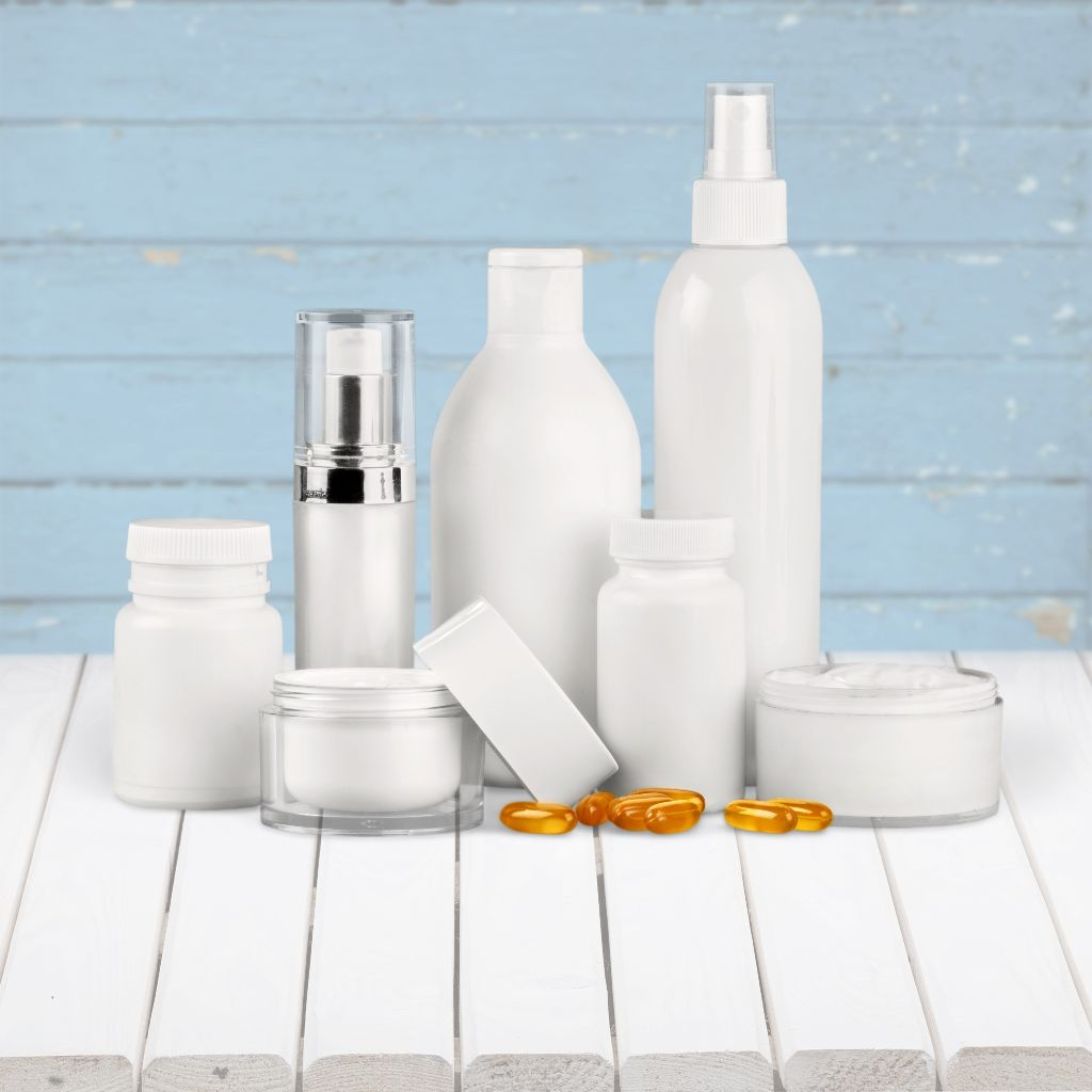 nine bottles and pots for personal care on white wooden surface. In front of light blue background