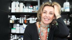 Savéria Coste, CEO of Garanci in front of a cosmetics shelf, smiling