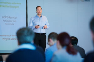Immo Sander, Head of Packaging Development at Werner & Mertz speaks in front of an audience