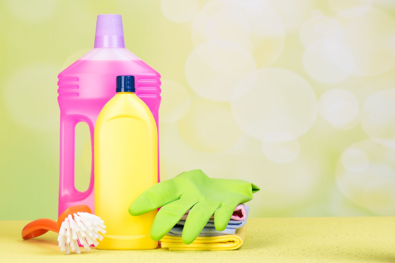 a pink and a yellow bottele of detergenzs with green gloves