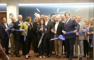 A group of laughing, cheerful-looking people holding oversized scissors and pieces of the ribbon they just cut in their hands at the opening of Pilot Chemical's new headquarters.