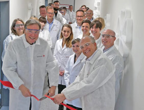 about 10 laboratory people cutting a red ribbon at the opening of the the application laboratory of symrise