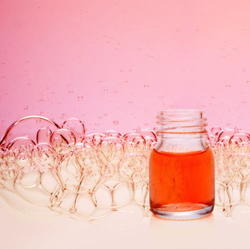 red liquid in a small glas in front of pink bubbles