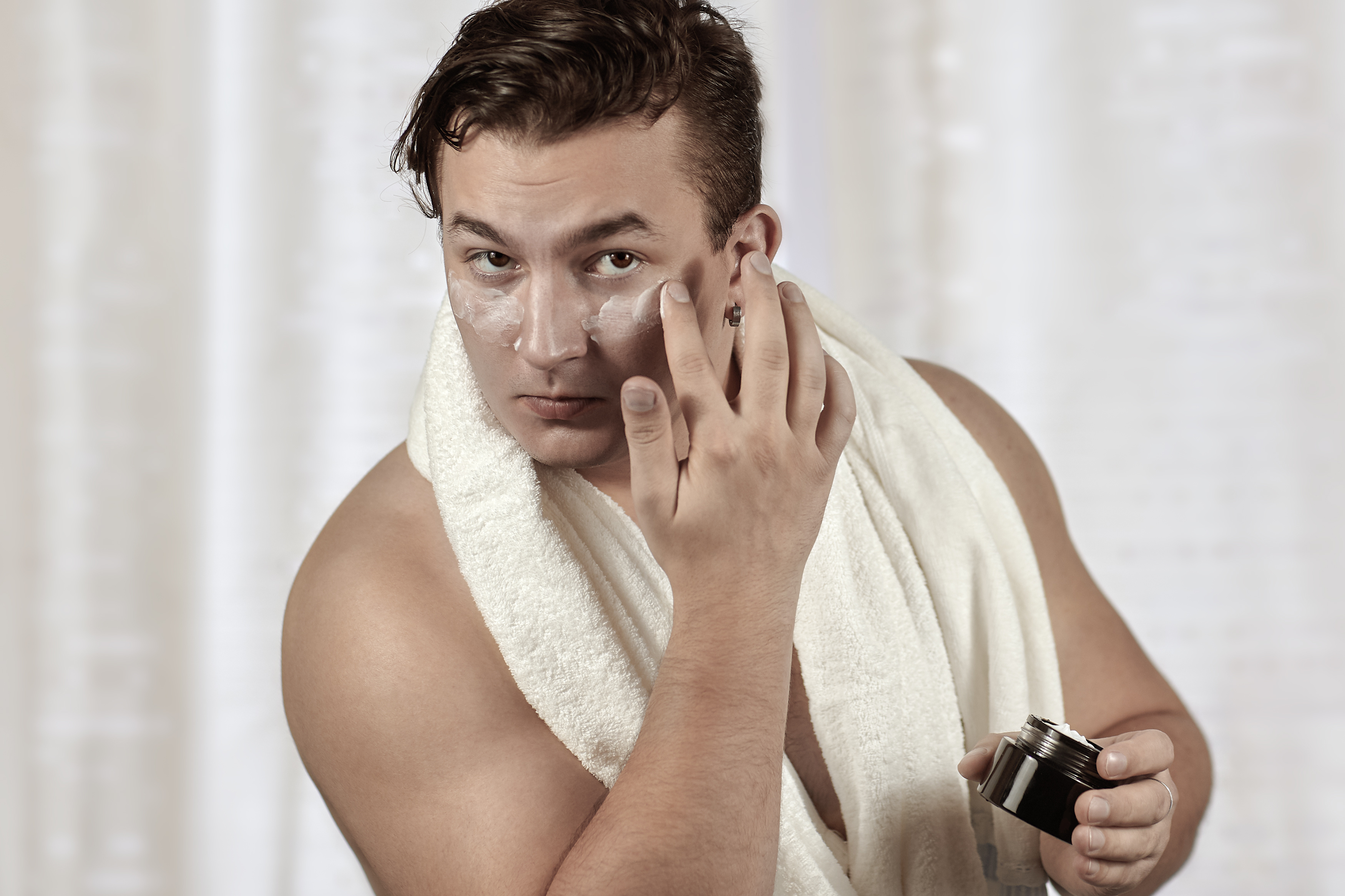 Young handsome caucasian man applying cream under the eyes. Caring face, metrosexual daily routine in the bathroom. Indoors, copy space.