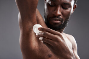 Pleasant young afro American man using his deodorant after shaving his armpits