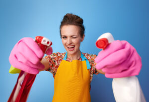 Big cleaning time. happy modern woman with rubber gloves using bottles of cleaning detergent as guns against blue background