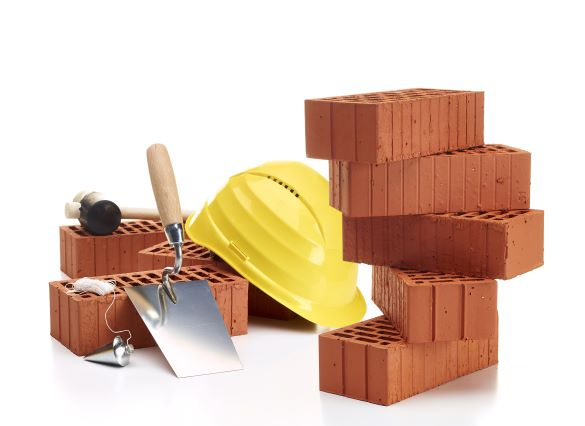 Brick trowel and yellow construction helmet with some bricks as symbol for new construction
