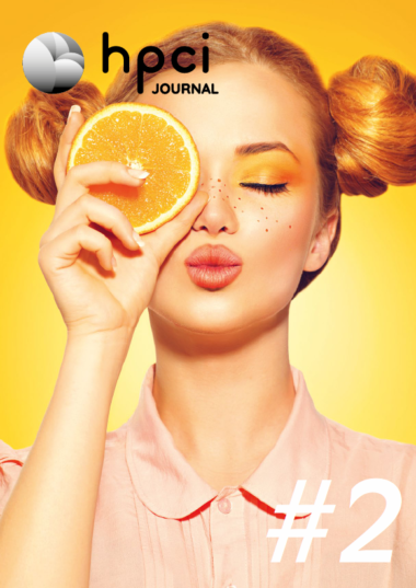 Cover HPCI Journal #2 showing a red-haired young women holding a slice of orange in front of her right eye, eyes closed, mouth like kissing. Background of the foto is yellow-orange