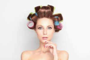 Young woman with coloured curlers in brunette hair