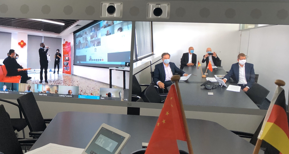 Group of people sitting a meeting room wearing masks in order to protect each other from covid-19. Occasion is the opening of a new productionsite in China by Symrise