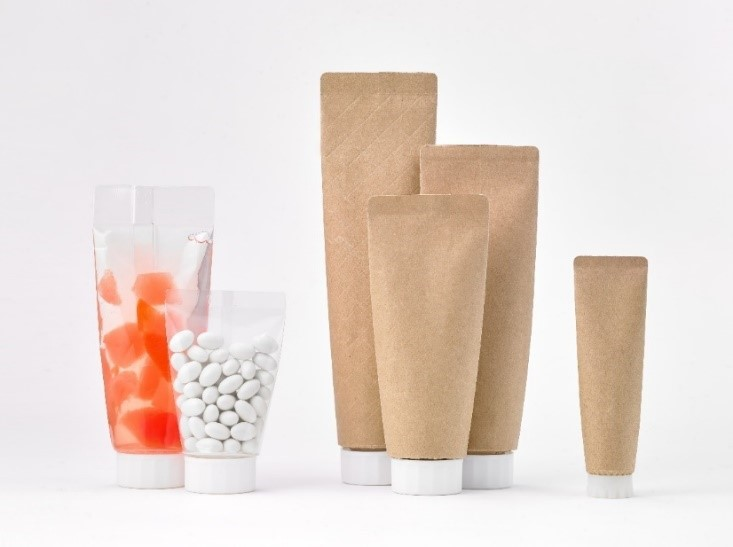 four brownish paper-based tube-pouches standing beside conventional plastic tube pouches