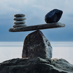 Symbol of scales is made of pebbles on the sea boulder