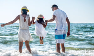 A family (man, women, little girl) on the beach holding hands and going into the see.. the sun is shining.