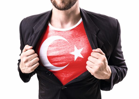 men - only the body is visible - opens his jacket and shows the Turkish Flagg on his T-shirt.